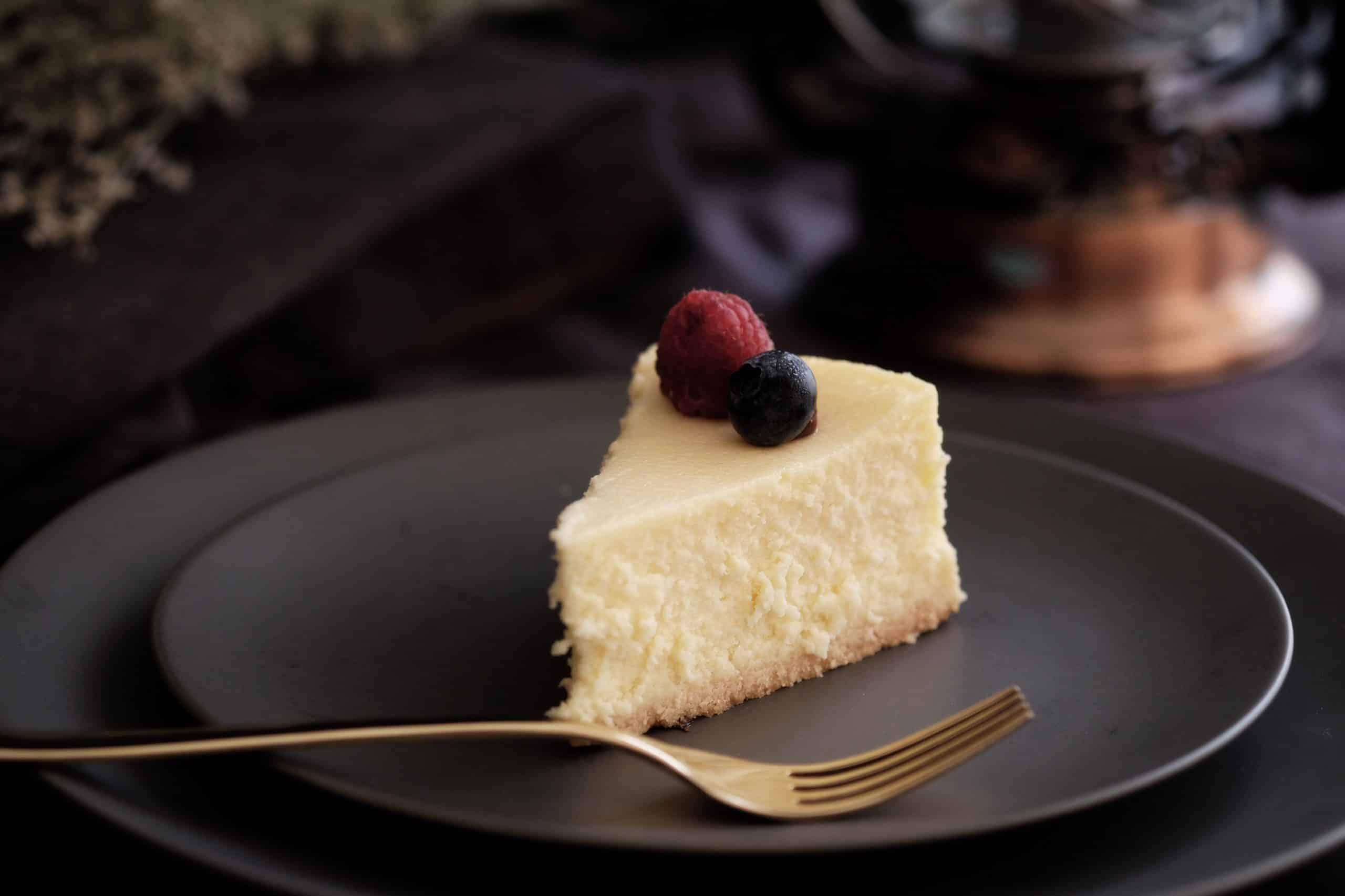part de cheesecake avec fruits rouges dessus dans une assiette noire avec fourchette dorée à côté